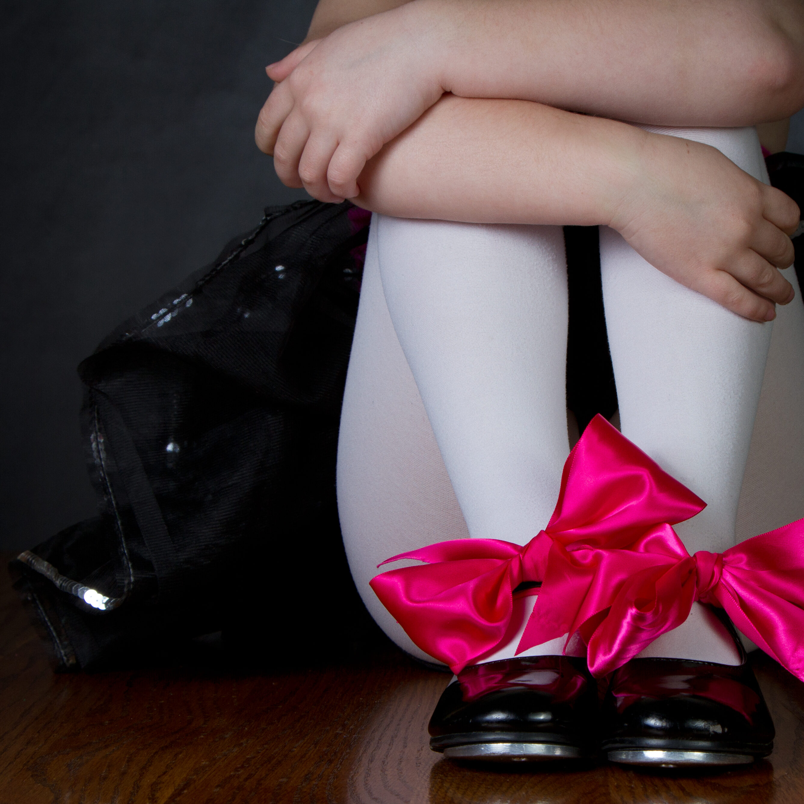 Tap shoes on a little girls feet, dark background room for copy space
